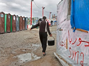 Young adult carries water to his makeshift home in preparation o