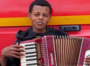 Young boy playing the accordian in the Calais Jungle.